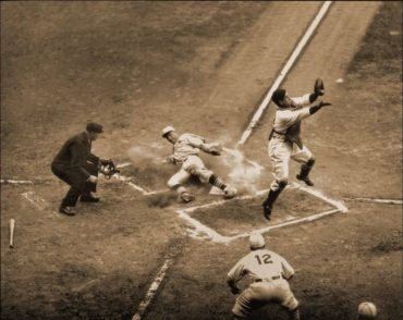 Navin Field, Detroit, MI, October 8, 1934 – Cards Jack Rothrock slides home safely under a leaping Mickey Cochrane of the Tigers in World Series action